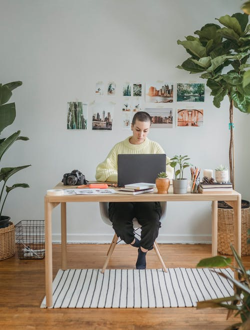 Full body of concentrated female photographer sitting at table with photo camera and browsing netbook while working remotely
