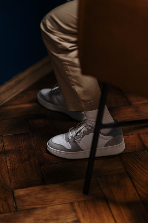 Person in Brown Pants and White Sneakers