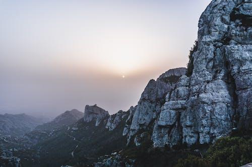 Rough rocky mountains under sun in haze