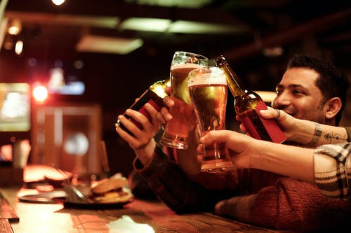 People Holding Drinking Glasses With Beer
