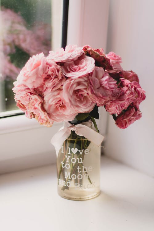 Bouquet of fresh rose arranged in transparent glass vase decorated with pink bow and declaration of love on white windowsill