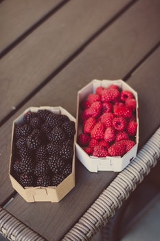 Raspberries And Blueberries On Top Of Table