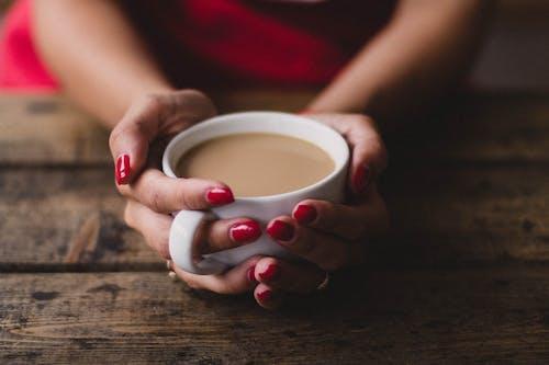 妇女拿着杯咖啡