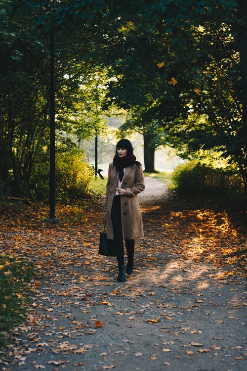 Full length of woman with bag and in warm clothes walking in autumn park in sunny day