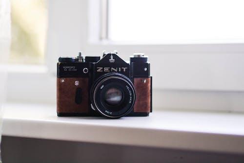 Retro photo camera on windowsill indoors