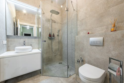 Modern bathroom interior with shower cabin and mirror in house