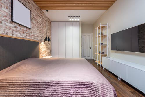 Bed with cover under empty panel on brick wall against television with black screen above cabinet at home