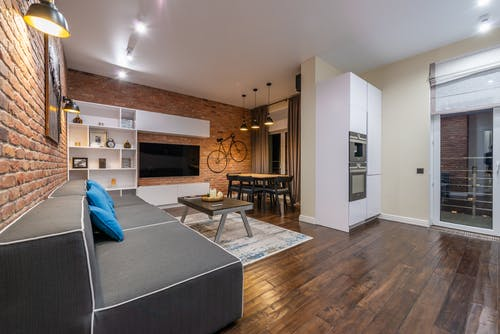 Modern loft living room with sofa against tables and built in oven in house with parquet and brick walls