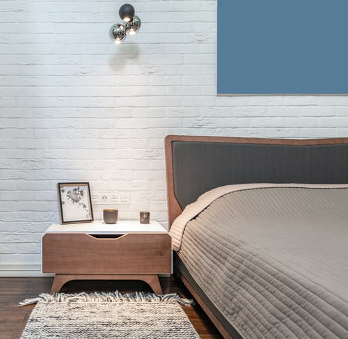 Modern bedroom interior with furniture against whitewashed brick wall