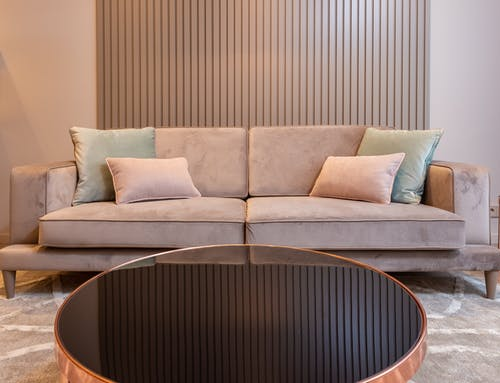 Stylish living room with cozy couch with soft pillows and round coffee table