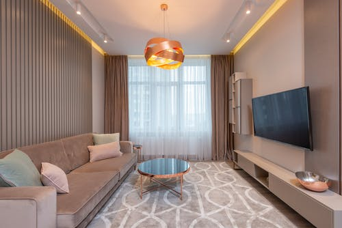 Spacious living room with comfortable couch with soft pillows near coffee table beneath creative luminous chandelier