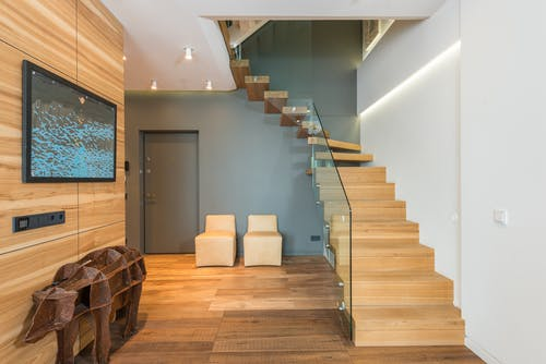 Contemporary stylish house hallway interior with creative statue under TV set cozy chairs and wooden stairway