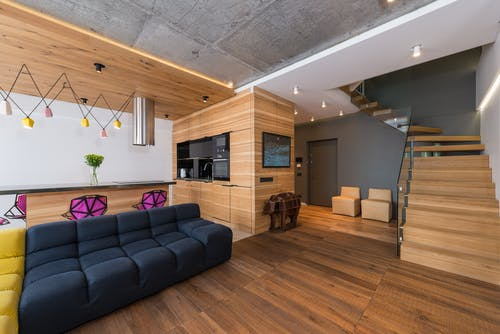 Black Leather Couch on Brown Wooden Parquet Flooring