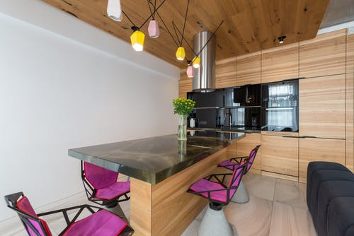 Stylish interior of contemporary kitchen with built in microwave and oven with stylish chairs around marble counter