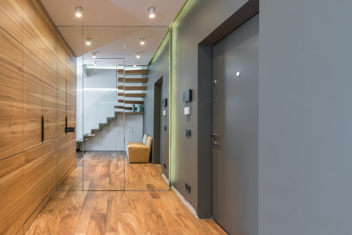 Empty hallway with door and big mirror with wooden closet and parquet floor leading to staircase