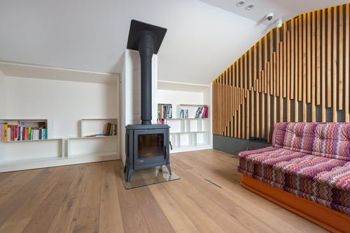 Black Fireplace Near Red and White Striped Sofa