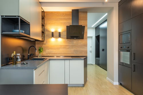 Interior of contemporary kitchen with counter under shelves and cabinets with microwave and oven with hood