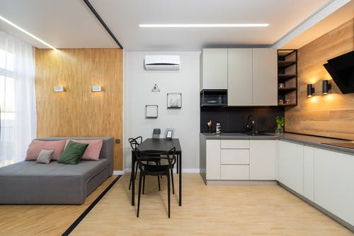 Interior of spacious light studio apartment with sofa with cushions near window and table with chairs in kitchen with modern appliances
