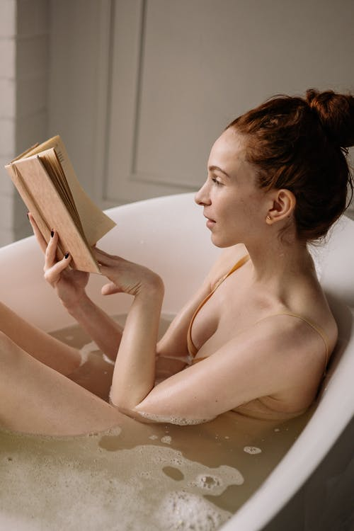 A Woman Reading a Book while in the Bathtub