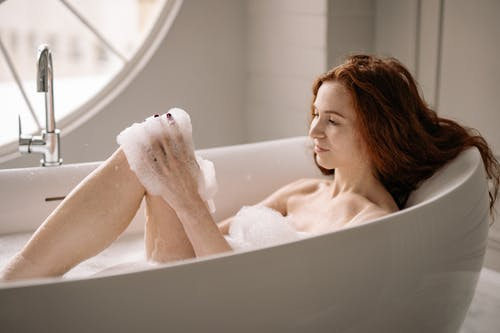 Photo of a Topless Woman with Red Hair Taking a Bath