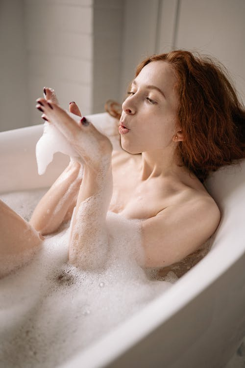 Woman in a Bathtub Blowing Soap Bubbles on Her Hand