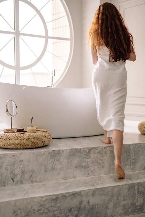 A Woman in Bath Towel Going into the Bathtub