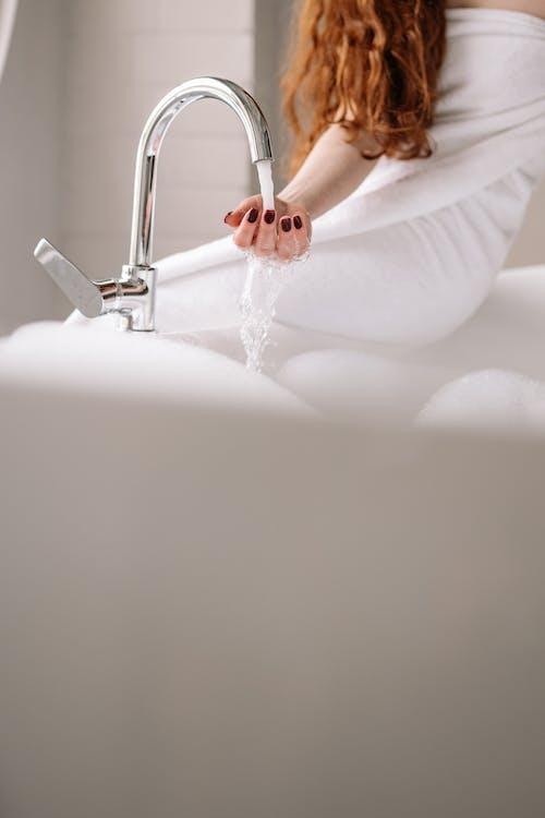 Woman in White Dress Lying on White Ceramic Bathtub