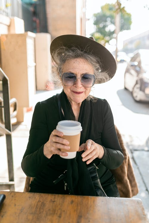 Woman in Black Dress Holding White Disposable Cup