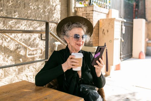 Woman in Black Using Her Smartphone While Having Coffee