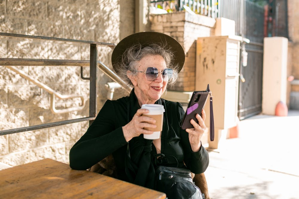 Woman in black using her mobile phone while having coffee. | Photo: Pexels