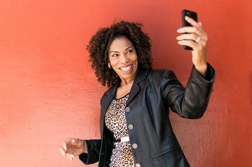 Woman in Black Leather Jacket Holding Black Smartphone