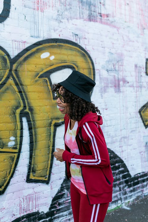 Woman in Red and White Sports Jacket Standing Beside Wall with Graffiti