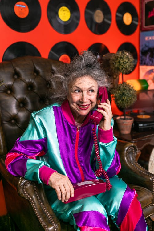 Elderly Woman Sitting on Brown Leather Chair Using Telephone