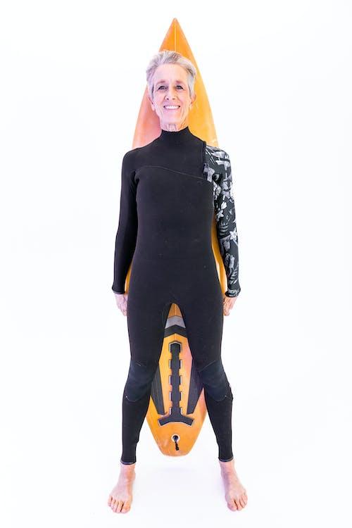 Woman in Black Swimwear Holding A Surfboard