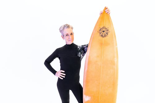 Woman in Black Long Sleeve Shirt Holding Orange Surfboard