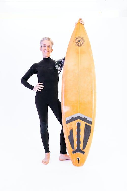 Woman Standing Beside A Surfboard