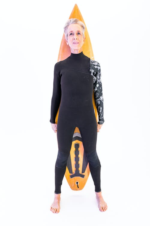 Woman in Black Active Wear Standing With A Surfboard
