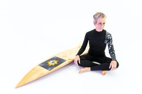 Woman in Black Long Sleeve Shirt and Black Leggings Sitting on Floor Beside A Surfboard