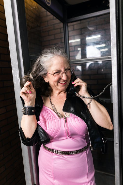 Woman in Black Leather Jacket In A Phone Booth
