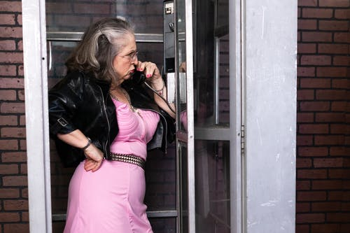 Elderly Woman Calling Inside A Phone Booth