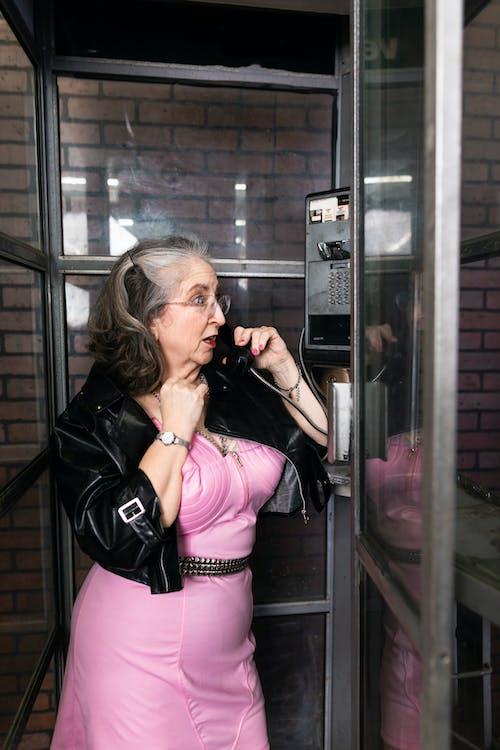 Elderly Women Calling Inside A Phone Booth