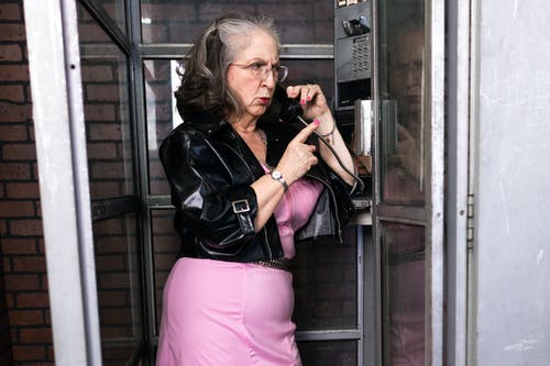 Woman in Black Leather Jacket And Pink Dress Inside A Phone Booth