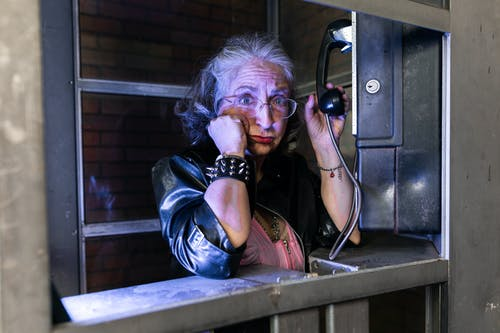 Woman in Black Leather Jacket Standing In A Phone Booth