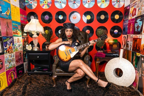 Woman Sitting On A Leather Chair Holding A Guitar