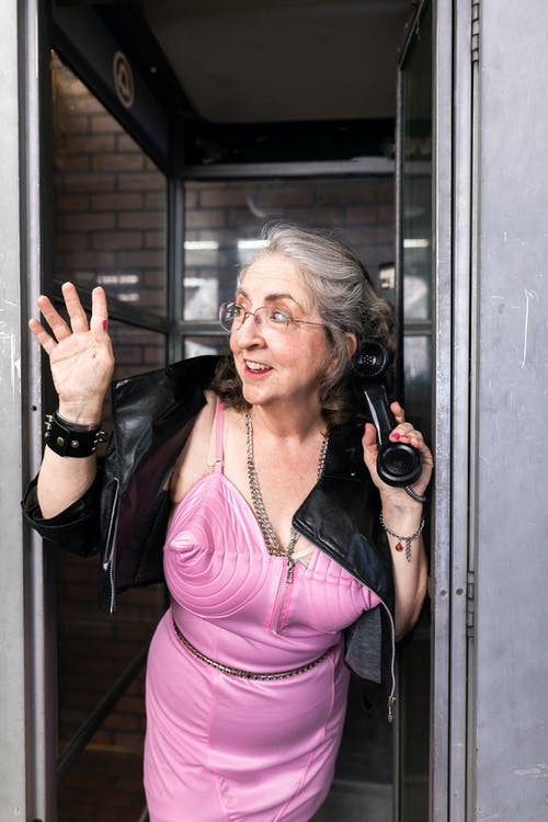 Woman in Pink Dress Inside A Phone Booth