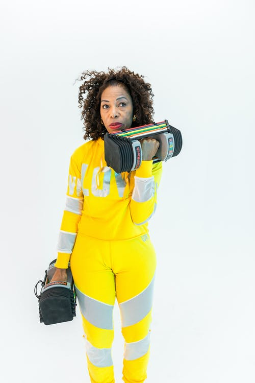 Woman in Yellow and Gray Long Sleeve Sportswear Holding Weights