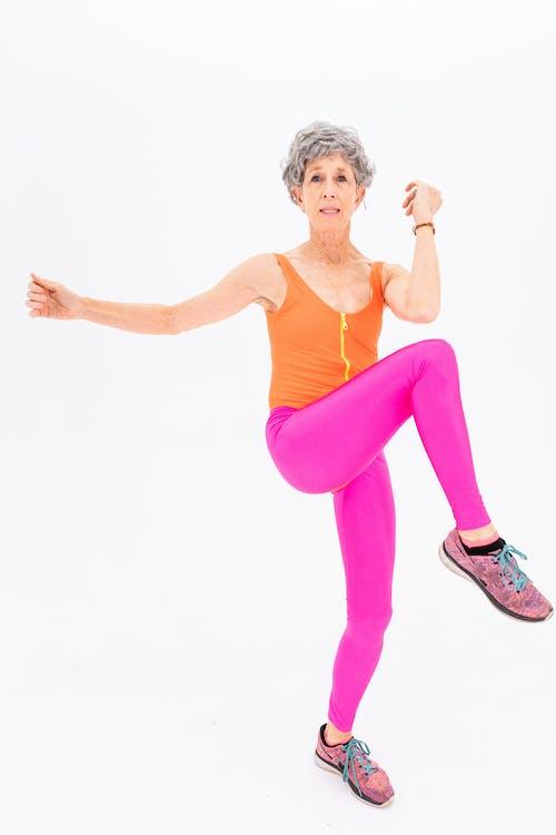 Woman in Purple Tank Top and Pink Leggings Doing Aerobics