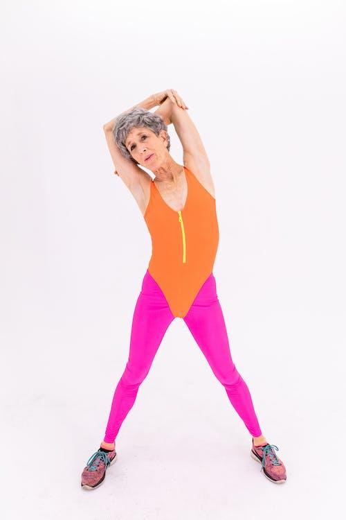 Woman in Orange Tank Top and Purple Leggings
