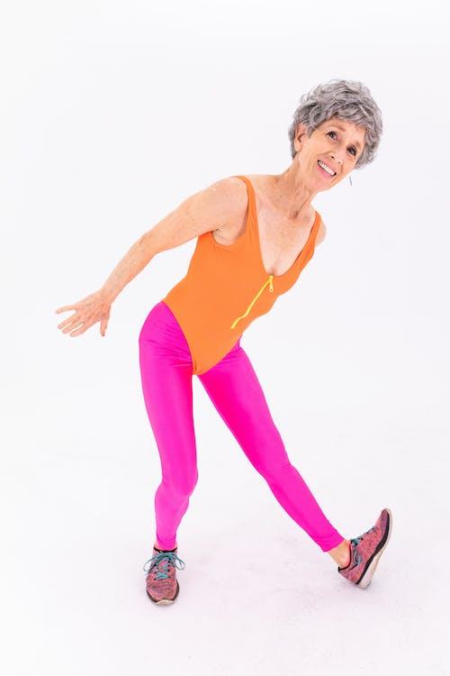 Woman in Orange Tank Top and Pink Leggings