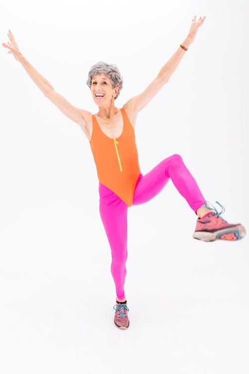 Woman in Orange Tank Top and Pink Leggings Doing Aerobics